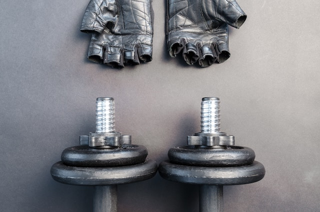 two dumbbells and boxing gloves