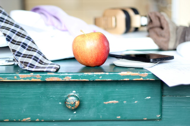 a nightstand with an apple on top of it