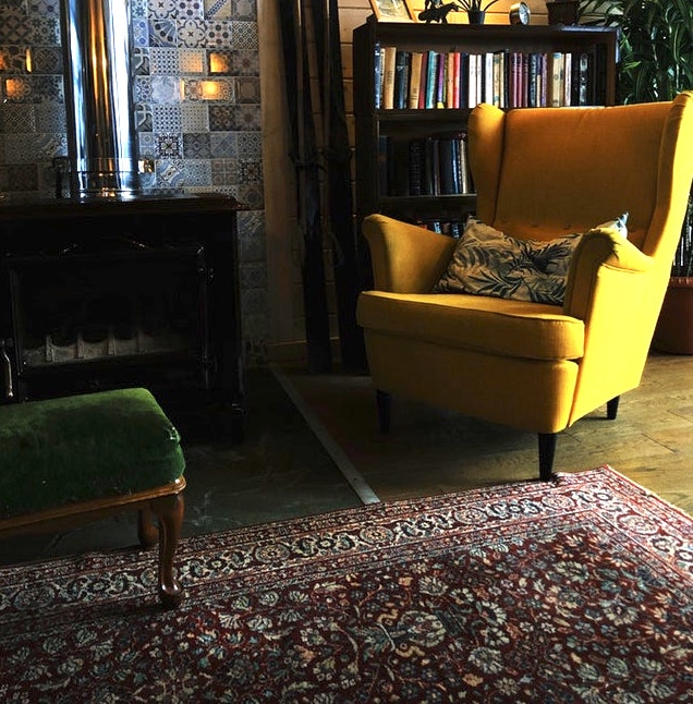 a bright yellow chaise on an ancient rug