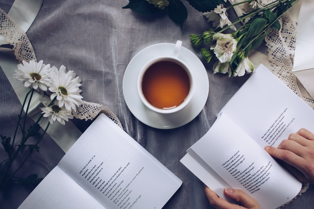 a book surrounded by a cup of tea and flowers