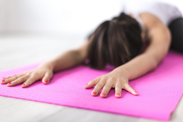 a girl stretching on a yoga mat