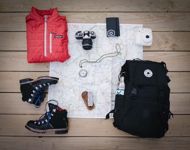 winter boots, jacket, camera and a backpack laid out
