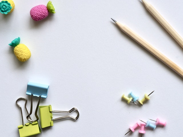 paper clips, pencils and erasers against a white backdrop