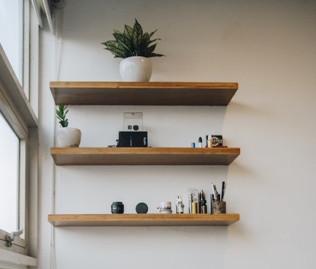 a shelf with plants and stationery