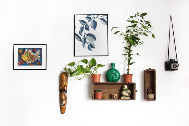 Paintings on the wall with accent decor of masks and vases