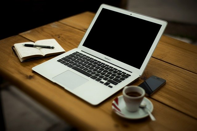A computer and a cup of espresso on a wooden table