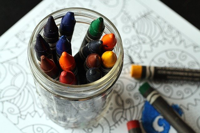 A cup of crayons on a painting book
