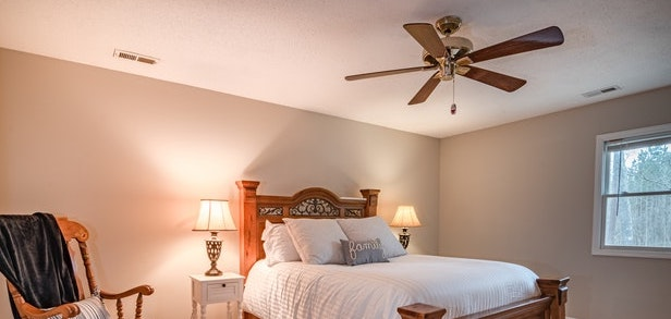 a well-lit bedroom with a ceiling fan