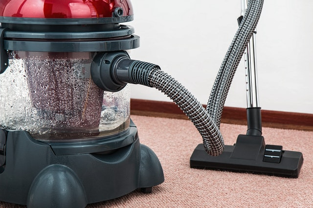 A vacuum with an attachment at work on a carpet