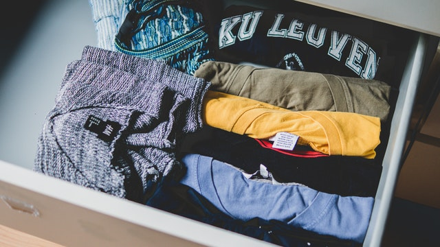 a drawer full of folded t-shirts and sweaters