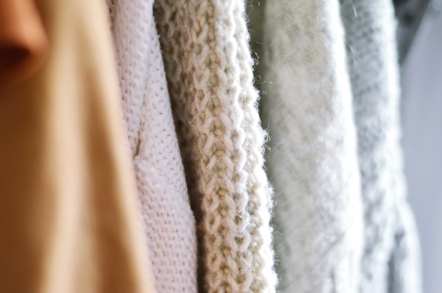 a line of warm wool sweaters hung