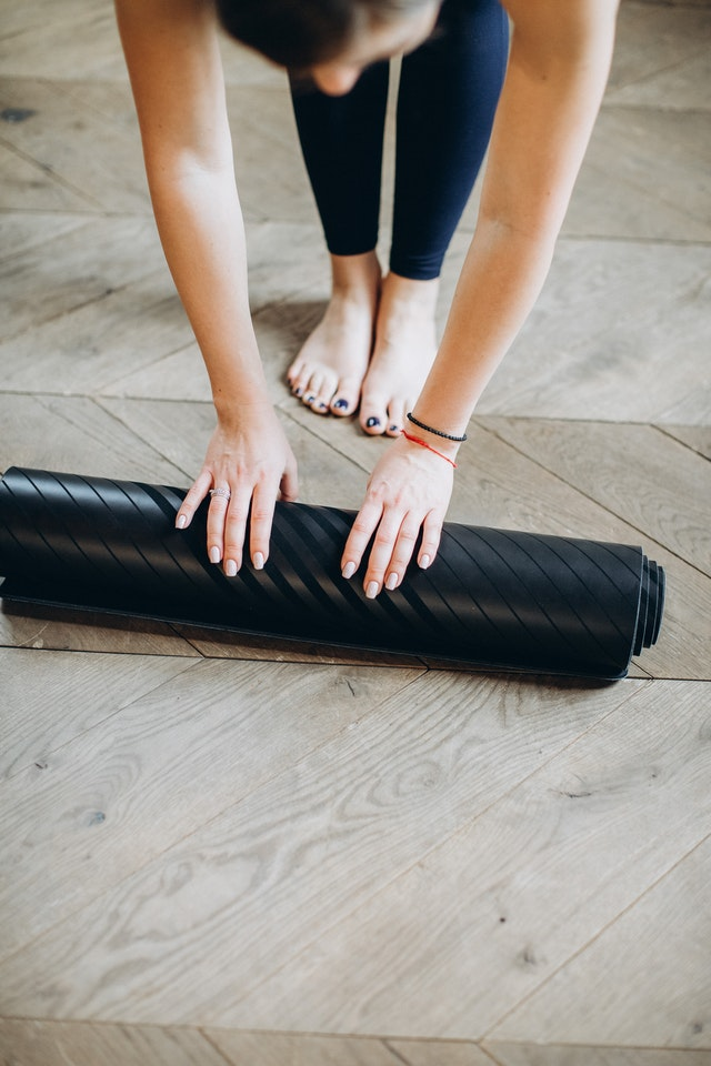 A girl rolling up her exercise mat off the floor.
