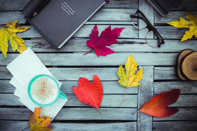 A journal surrounded by a bunch of colorful fall leaves, a pair of reading glasses and a cup of coffee.