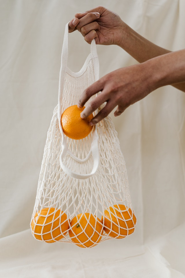 A hand placing oranges in a cloth bag