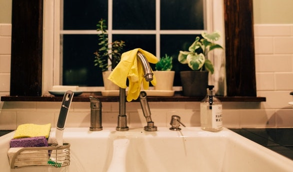 A kitchen sink with gloves hanging on top the faucet