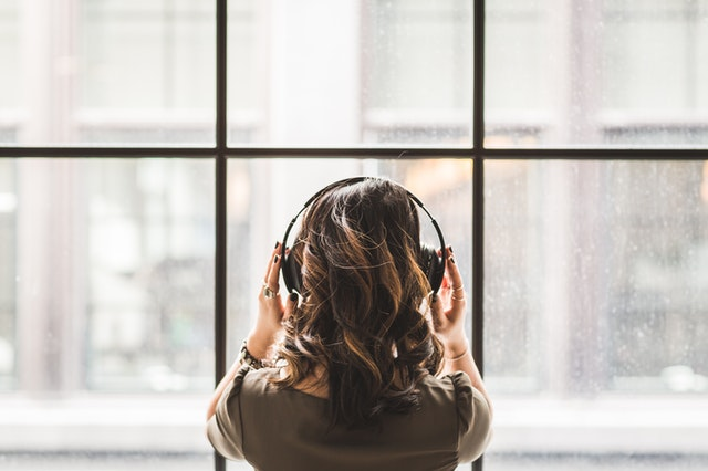 A girl listening to music on her headphones facing backwards