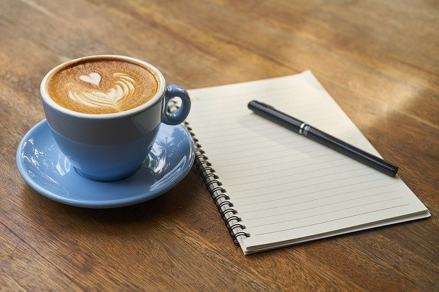 A cup of coffee next to a notebook on a wooden table