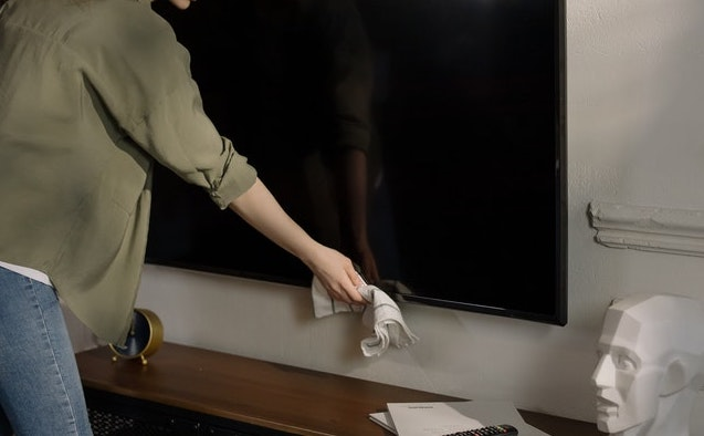 Woman cleaning a TV screen with a cloth