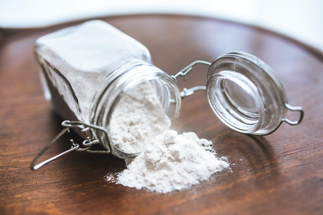 A jar of baking soda on a wooden table