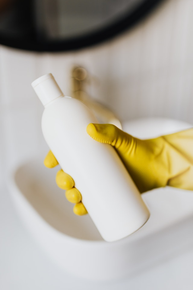 A cleaning bottle in the hands of a person wearing yellow cleaning gloves
