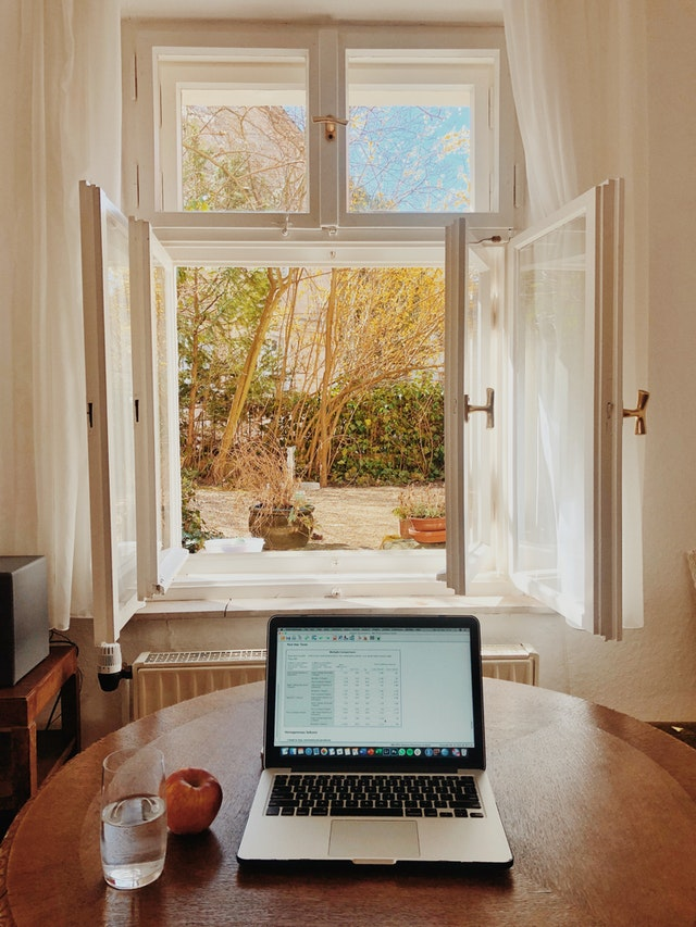 A work desk by the window with natural light and fresh air