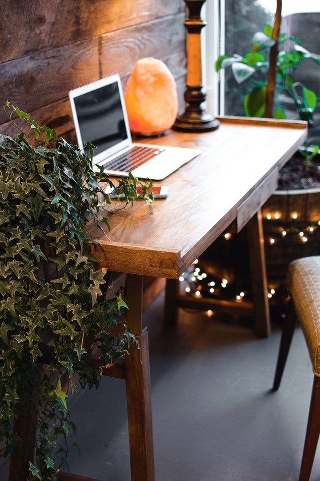 A wooden desk by the window surrounded by plants and a Himalayan salt lamp