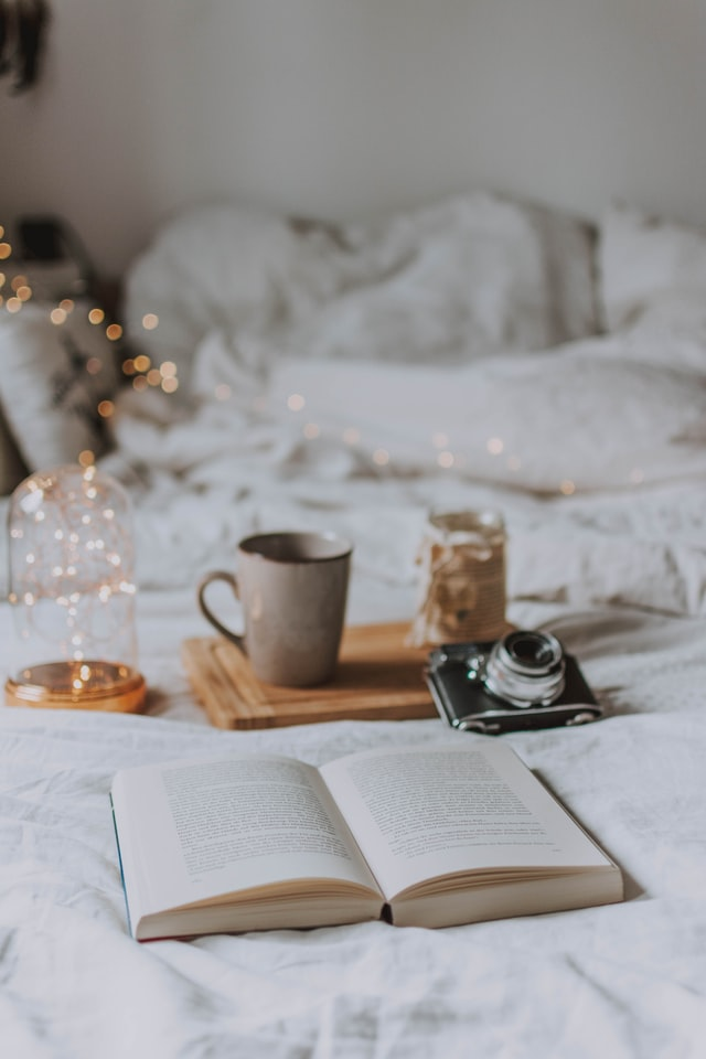 A book laying open on a bed surrounded by fairy lights, a camera and a cup of coffee