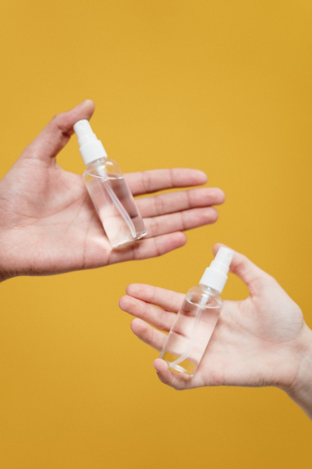 Two hands holding two clear spray bottles