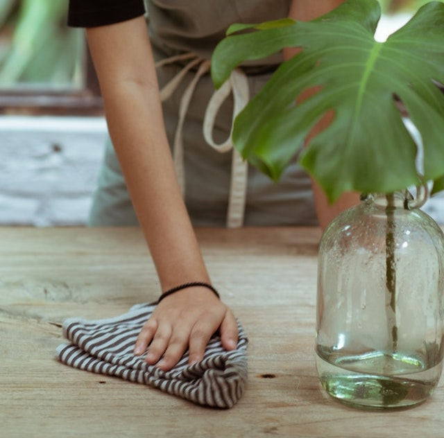 A hand cleaning a wooden table with a damp cloth