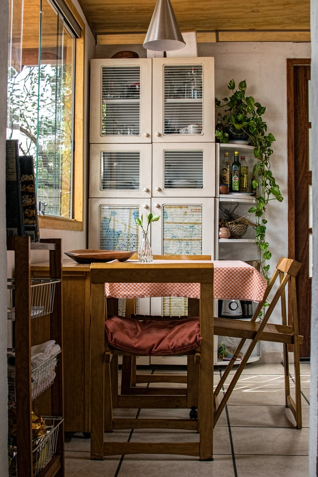 A kitchen cabinet by a small dinning nook