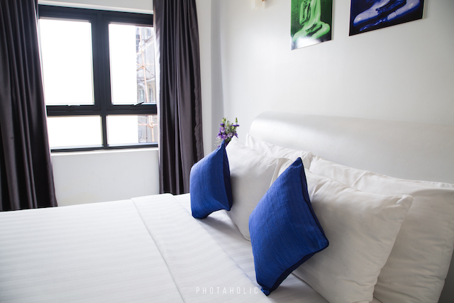 A clean bedroom with blue pillows and a plenty of sunlight