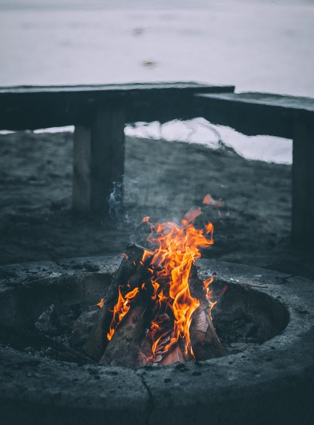 A fire burning inside a concrete fire pit