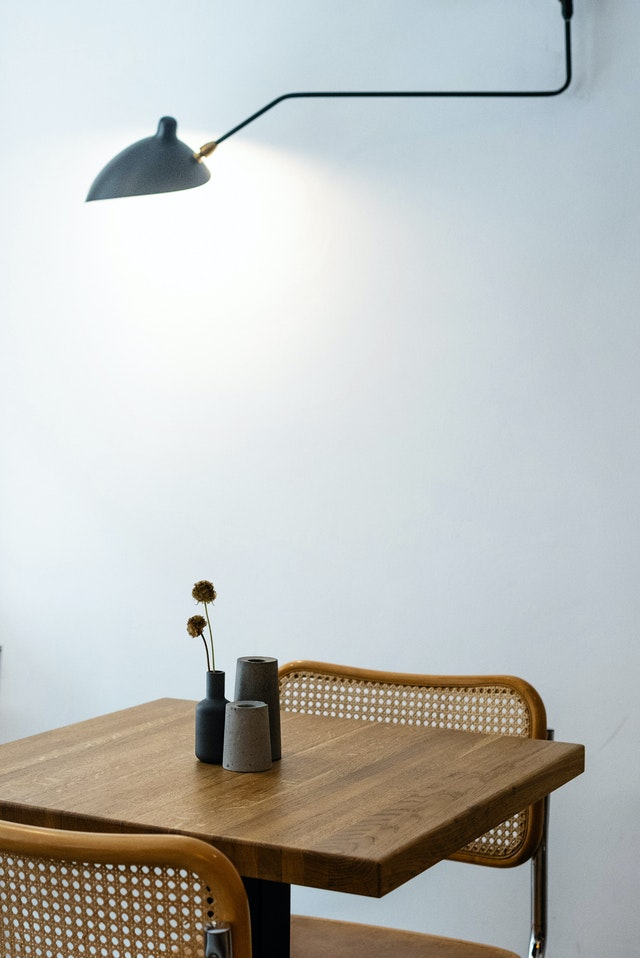 A modern light on a wooden table against a white wall