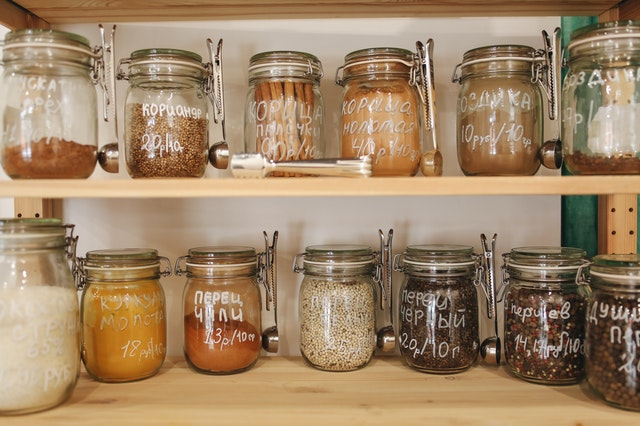 Glass jars filled with grains and spices in a pantry.