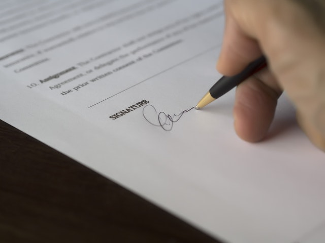 A hand signing a contract