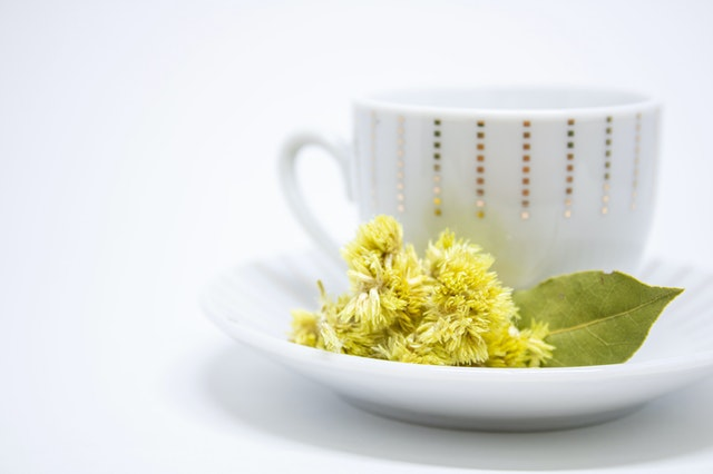 A white cup of tea with yellow flowers in the saucer.