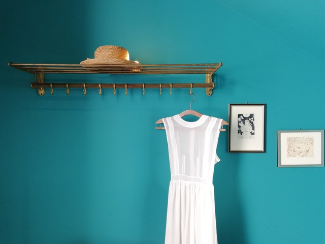 A blue wall with a white dress hanging in front of it