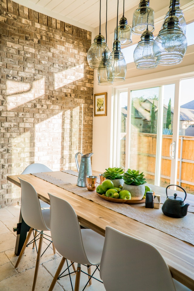 A bright dining room drenched in sunlight with succulents and a kettle on a wooden table