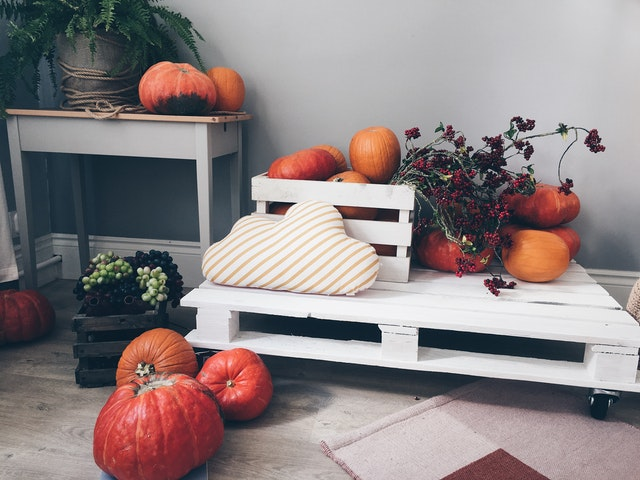 A few bright pumpkins surrounded by a crate of dried berries and flowers.