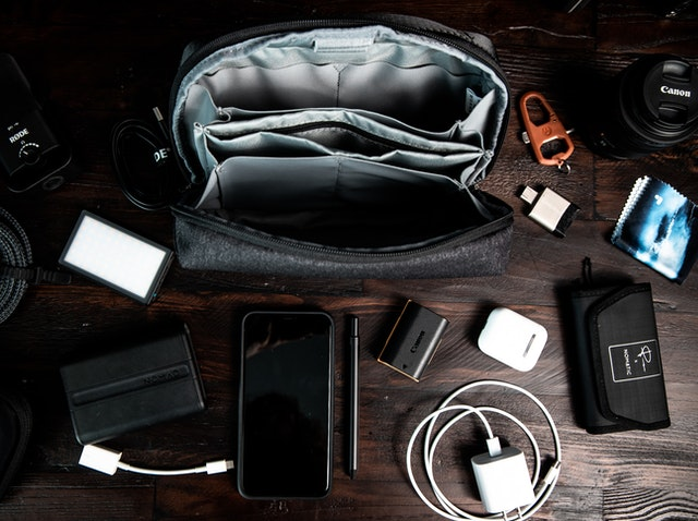 An overhead view of a work desk with a work bag and a few chargers and electronics.