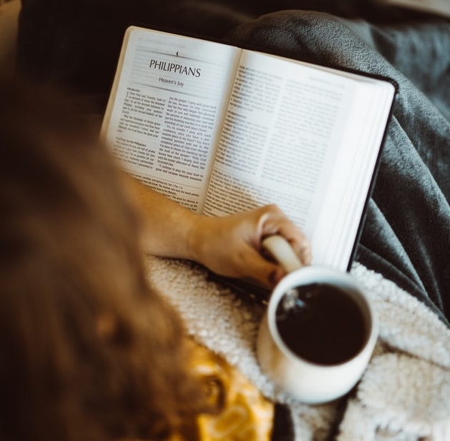One hand holding a hot beverage with a book in the other hand