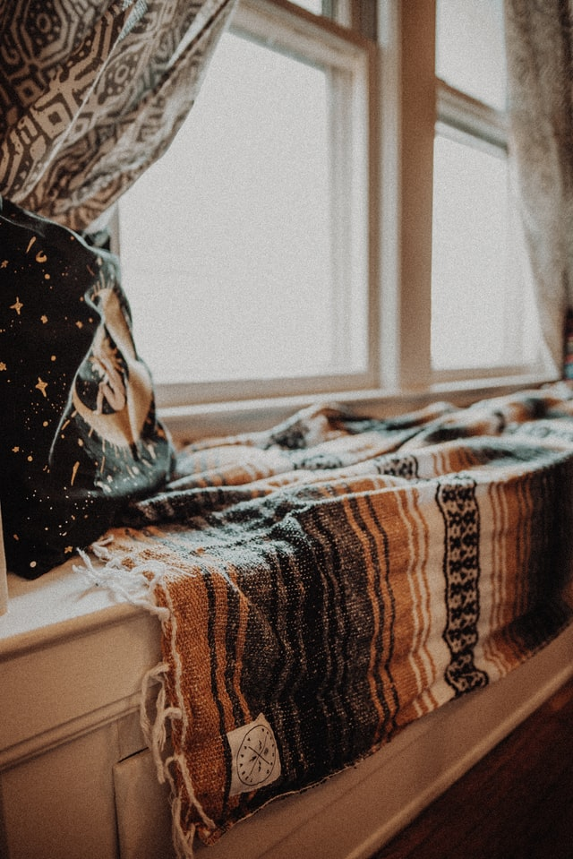 A nook by the window with a pillow, curtains and a warm blanket