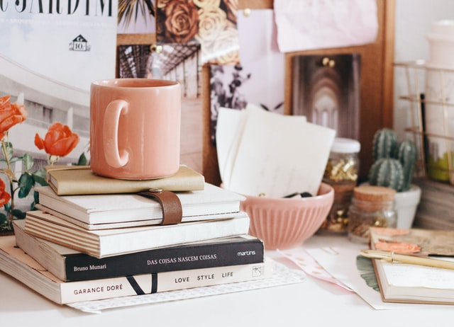 A coffee cup placed above a few books and diaries on a desk