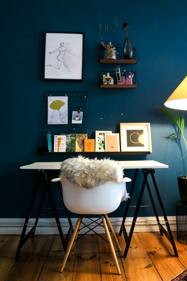 A deep blue wall with a desk in front of it
