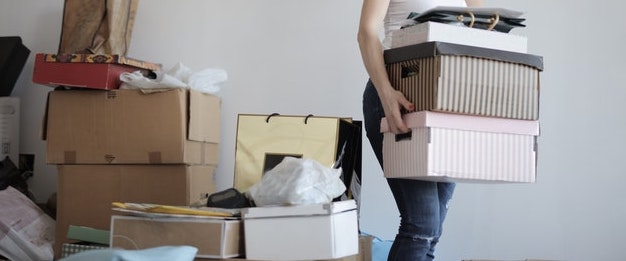 A girl carrying shoe boxes and clothes out of a frame.