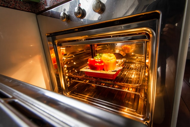 An open clean oven with food on a baking tray.