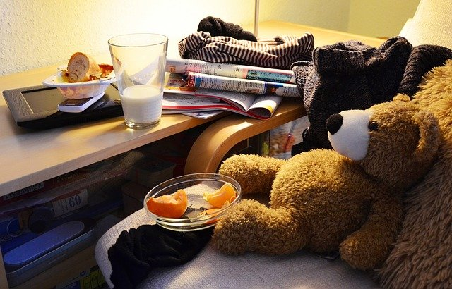 A teddy bear lying around with a half glass full of milk, oranges and books strewn around it.