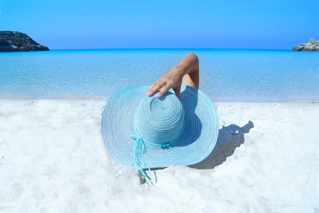 A girl laying on the beach with a big blue sun hat