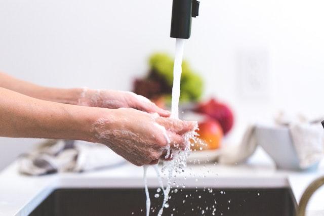 A pair of hands under a running kitchen faucet