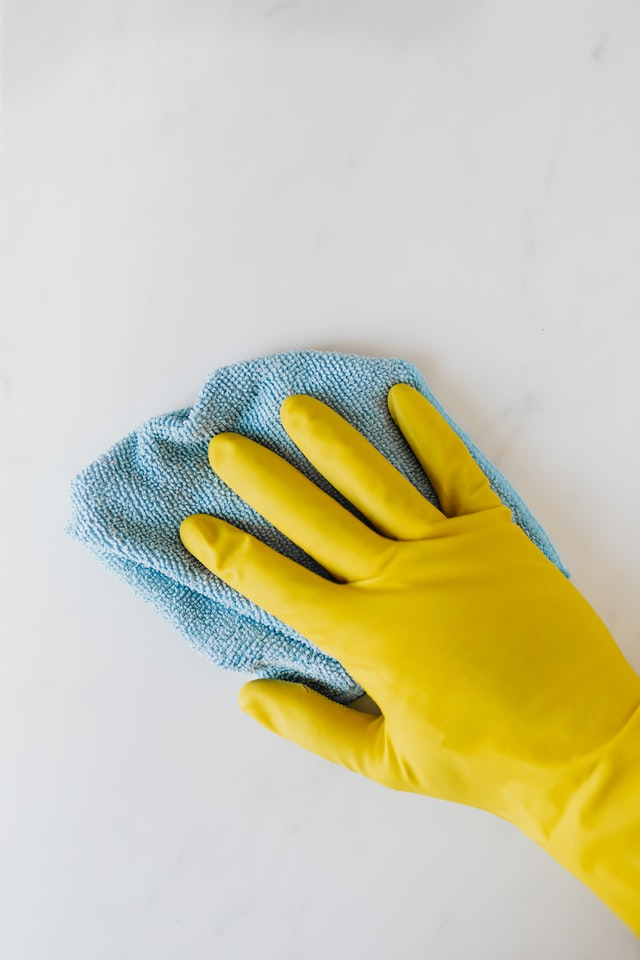 A hand in yellow rubber gloves with a cleaning cloth